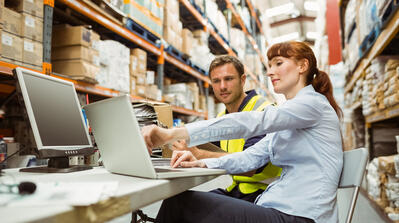Manager and Warehouse worker looking at laptop PC